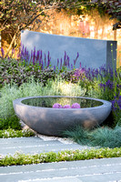 H U G: Healing Urban Garden; view of concrete circular water feature and grey stone slabs surrounded by Festuca glauca (blue fescue grass), Lavandula, Thymes   - Designer: Rae Wilkinson; Sponsor: Livi