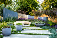 H U G: Healing Urban Garden; view of a modern patio with wooden bench and circular concrete water feature and containers amongst  Festuca glauca (blue fescue grass), Thymes, Lavandula, Nepeta. - Desig