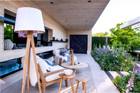 Modern patio with TV, lamp, wooden chairs, tables, made from Accoya (design by Nils Verweij), the path and flowerbeds with Persicaria bistorta 'Superba', Hesperis matronalis, Rosa 'Natasha Richardson'